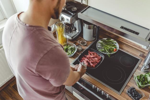 Junger mann, der rohes fleisch auf grillpfanne kocht