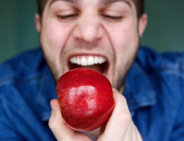 Junger mann, der roten apfel isst
