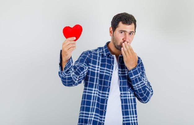 Junger mann, der rotes herz mit hand auf mund im hemd hält und schüchtern schaut