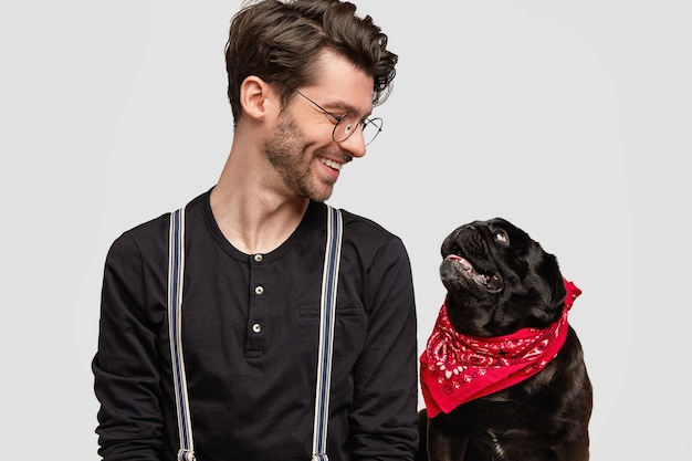 Junger mann, der rotes kopftuch und schwarzes hemd und seinen hund trägt