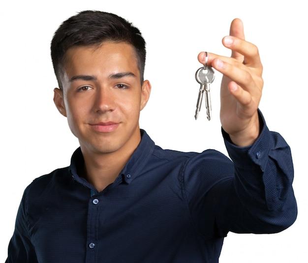 Junger mann, der satz hausschlüssel hält