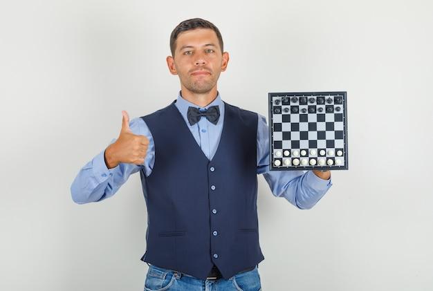 Junger mann, der schachbrett mit daumen oben im anzug hält