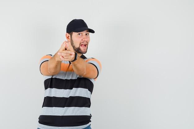 Junger mann, der schießgewehrgeste in t-shirt, mütze macht und munter, vorderansicht schaut.