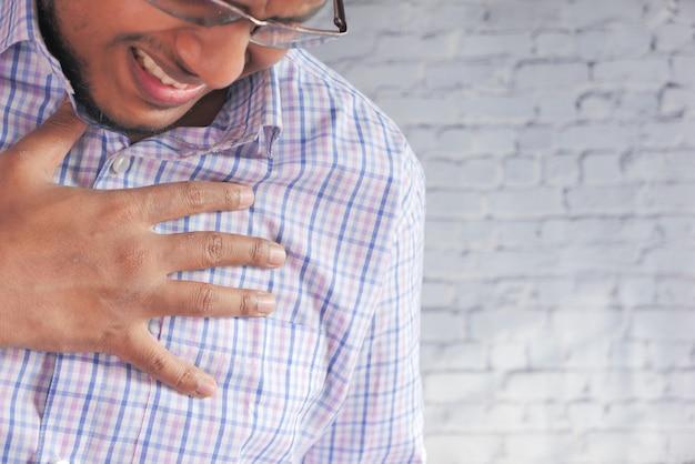 Junger mann, der schmerzen im herzen leidet und brust mit hand hält.