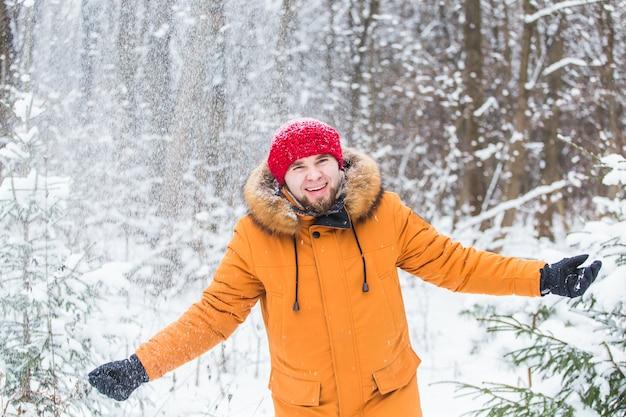 Junger mann, der schnee im winterwald wirft. kerl, der draußen spaß hat. winteraktivitäten.