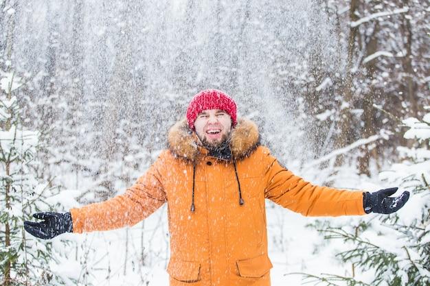 Junger mann, der schnee im winterwald wirft. kerl, der spaß draußen hat. winteraktivitäten.