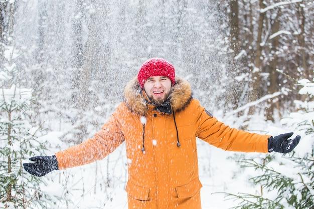 Junger mann, der schnee im winterwald wirft.