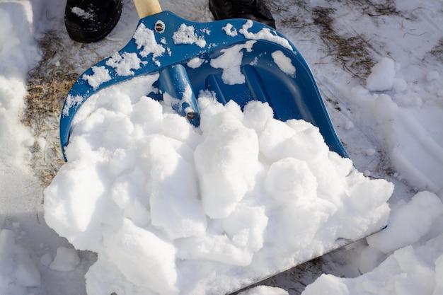 Junger mann, der schnee in der fahrstraße nahe der garage schaufelt