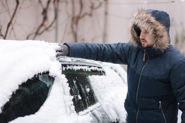 Junger mann, der schnee von der windschutzscheibe des autos im freien nahe der garage am wintertag reinigt