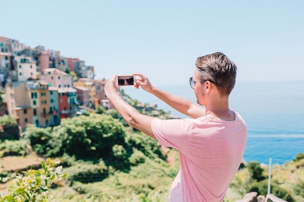 Junger mann, der schönes altes italienisches dorf selfie hintergrundes, cinque terre, ligurien, italien nimmt