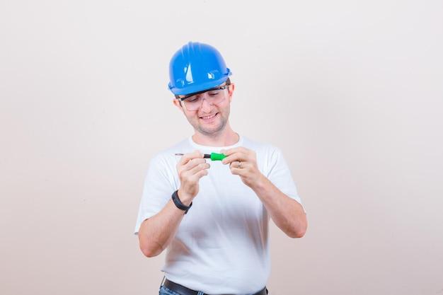 Junger mann, der schraubenzieher in t-shirt, jeans, helm hält und fröhlich aussieht