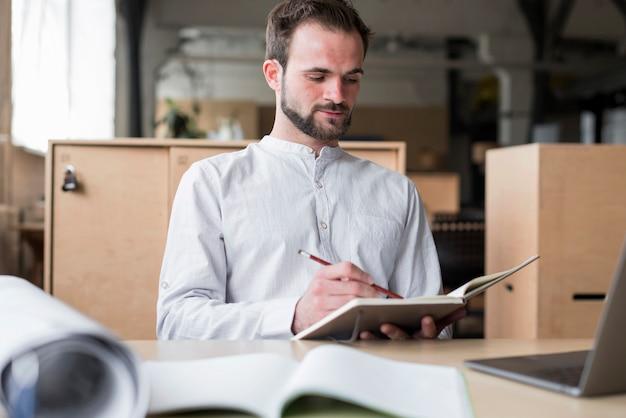 Junger mann, der schreiben auf tagebuch im büro hält