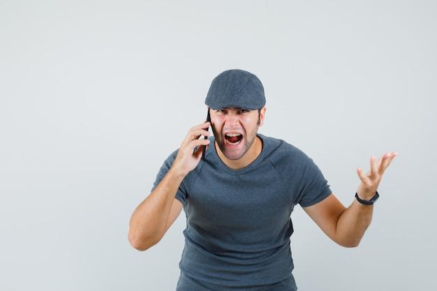 Junger mann, der schreit, während er auf handy in der t-shirt-kappe spricht und wütend schaut