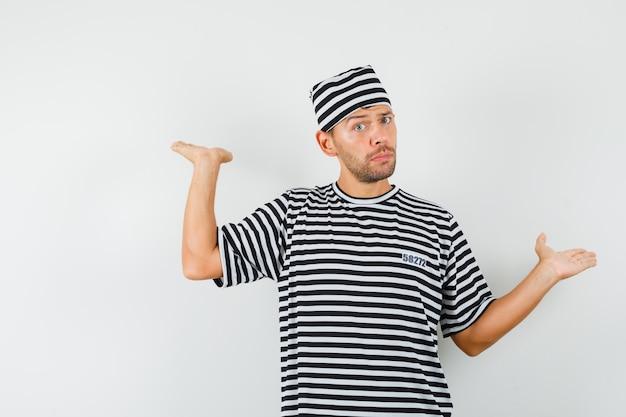 Junger mann, der schuppengeste in gestreiftem t-shirt, hut zeigt und unschlüssig schaut.