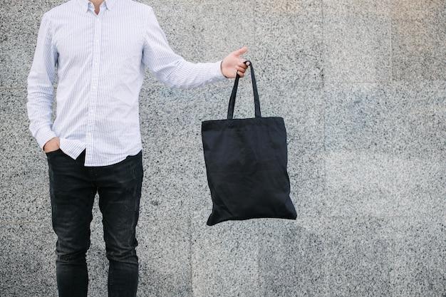 Junger mann, der schwarze textilöko-tasche gegen städtischen stadthintergrund hält. . ökologie- oder umweltschutzkonzept. schwarze öko-tasche für ihr design- oder logo-modell