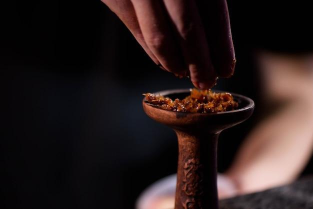 Junger mann, der schwarze verbrannte keramikschale für shisha füllt