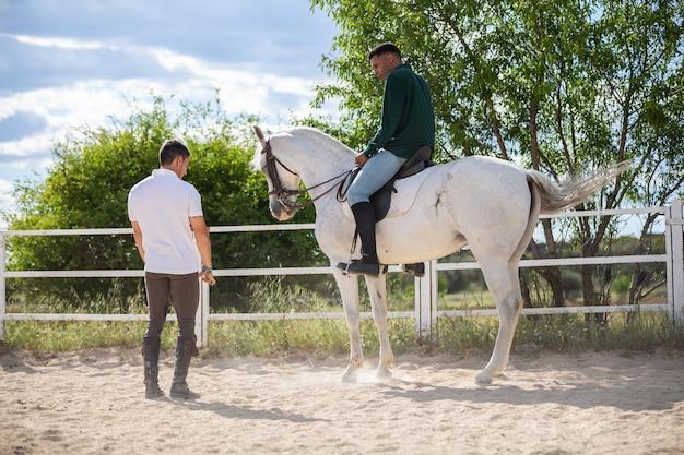 Junger mann, der schwarzen kerl unterrichtet, pferd in der koppel am bewölkten tag auf ranch zu reiten