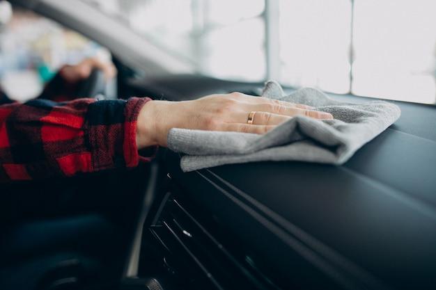 Junger mann, der sein auto mit lappen poliert
