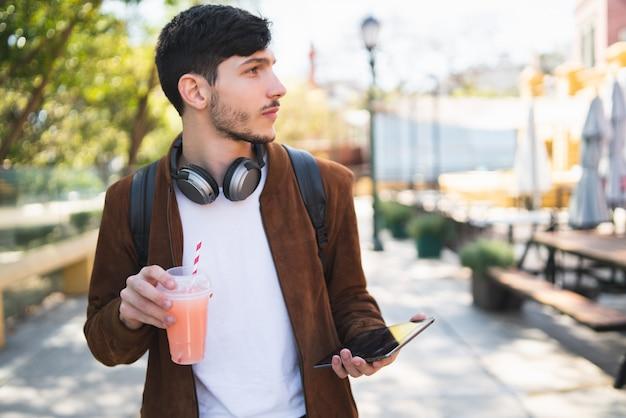 Junger mann, der sein digitales tablett benutzt.