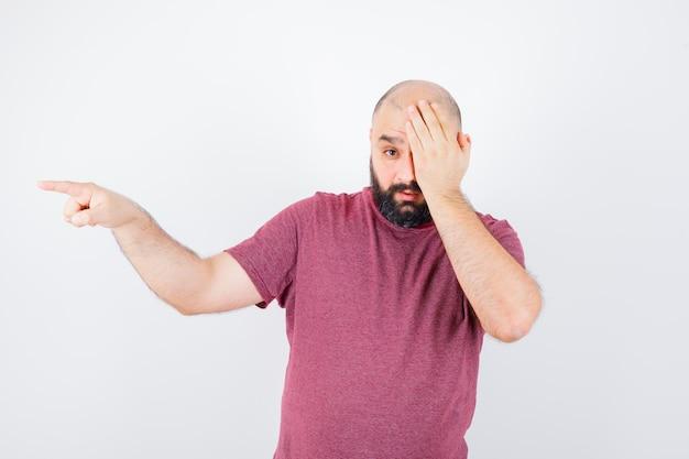Junger mann, der sein einziges auge bedeckt, während er in rosa t-shirt zur seite zeigt und beunruhigt aussieht. vorderansicht.