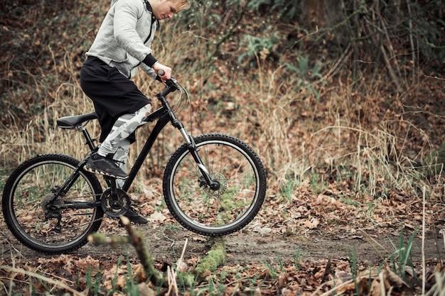 Junger mann, der sein fahrrad auf schotterweg fährt