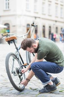 Junger mann, der sein fahrrad auf straße in der stadt repariert