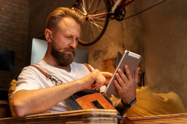 Junger mann, der sein fahrradgeschäft leitet Kostenlose Fotos