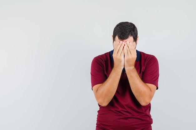 Junger mann, der sein gesicht mit händen im roten t-shirt bedeckt und traurig aussieht. vorderansicht.