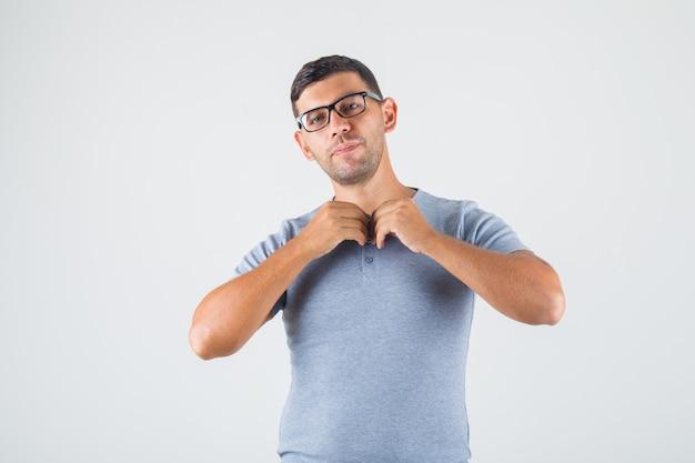 Junger mann, der sein hemd im grauen t-shirt, brillenvoransicht zuknöpft.