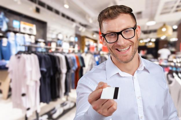 Junger mann, der sein kreditkartenschauen gibt