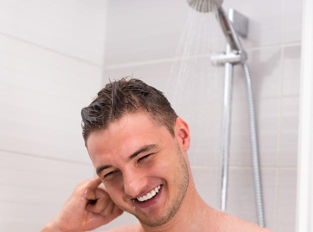 Junger mann, der sein ohr beim duschen säubert und unter fließendem wasser im modernen gefliesten badezimmer steht