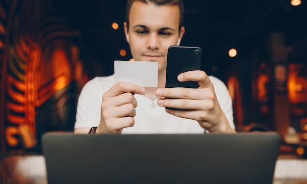 Junger mann, der sein smarphone und seine kreditkarte betrachtet