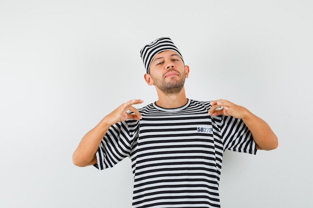 Junger mann, der sein t-shirt im gestreiften t-shirt, im hut zieht und stolz aussieht.