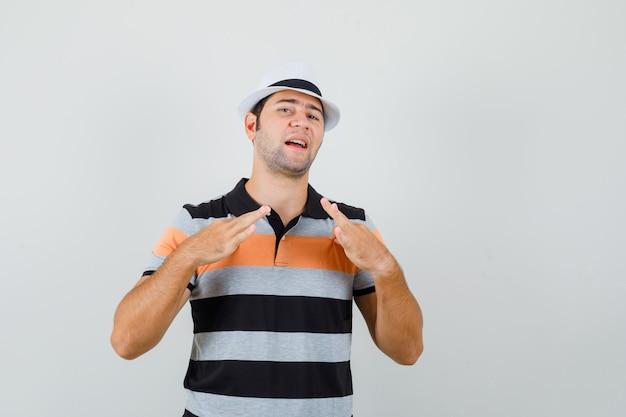 Junger mann, der sein t-shirt leicht in t-shirt, hut zieht und gelangweilt aussieht, vorderansicht.