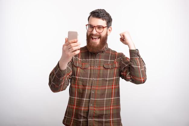 Junger mann, der sein telefon betrachtet, macht die gewinnergeste auf weißem hintergrund.