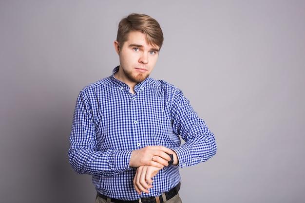 Junger mann, der seine armbanduhr über graue wand schaut.