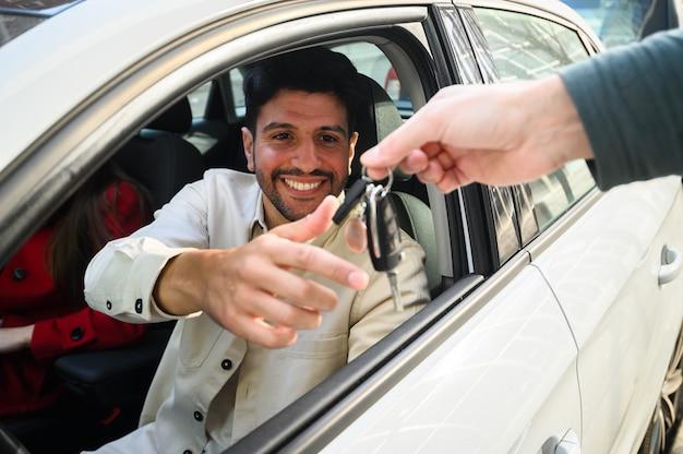 Junger mann, der seine autoschlüssel nimmt