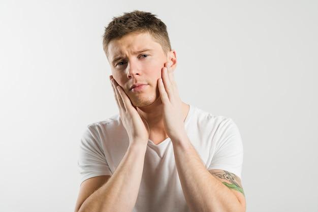 Junger mann, der seine backen mit zwei händen gegen weißen hintergrund berührt