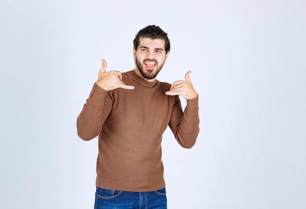 Junger mann, der seine beiden finger anhebt, wie das telefon auf einem weißen hintergrund zu übernehmen. foto in hoher qualität