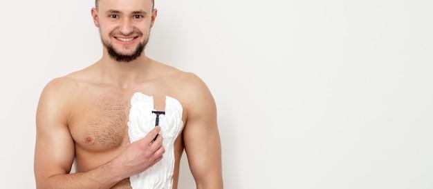 Junger mann, der seine brust rasiert