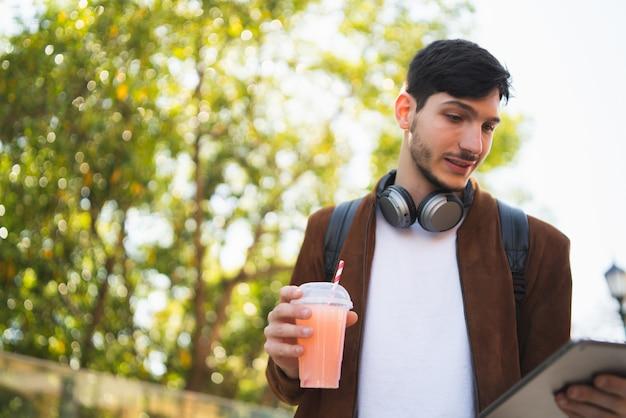 Junger mann, der seine digitale tablette verwendet.