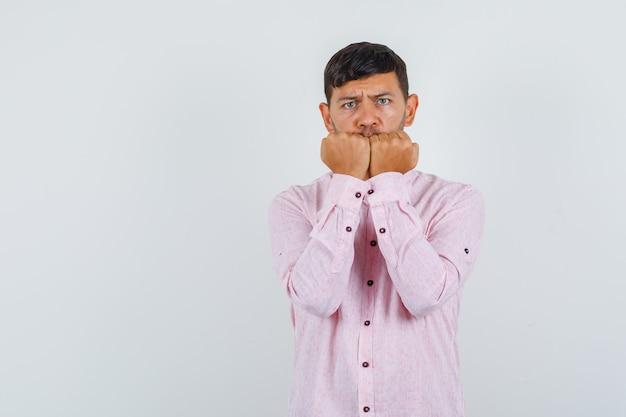 Junger mann, der seine fäuste im rosa hemd beißt und ängstlich aussieht. vorderansicht.