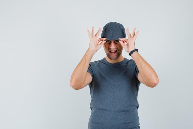 Junger mann, der seine mütze im grauen t-shirt hält und hübsch aussieht