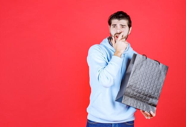 Junger mann, der seine tasche hält und auf die rote wand schaut