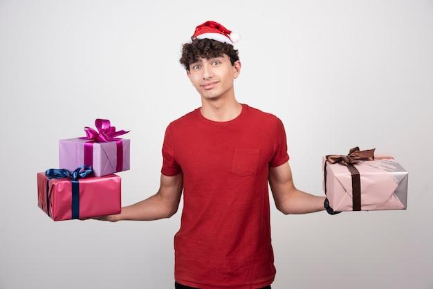 Junger mann, der seine weihnachtsgeschenke hält.