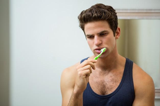 Junger mann, der seine zähne im badezimmer putzt