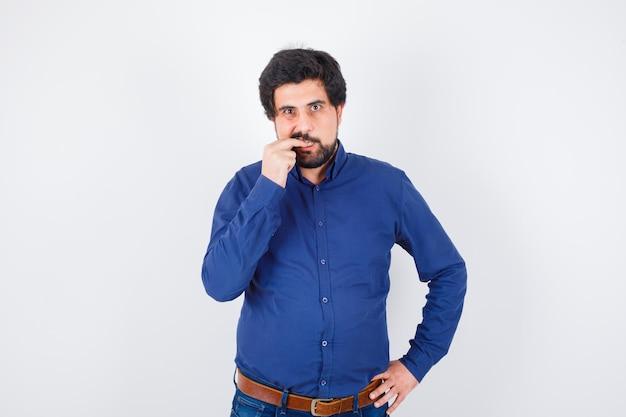 Junger mann, der seinen finger im königsblauen hemd beißt und ängstlich schaut. vorderansicht.