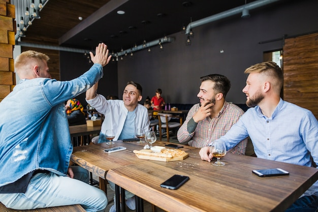 Junger mann, der seinen freunden im restaurant hoch fünf gibt