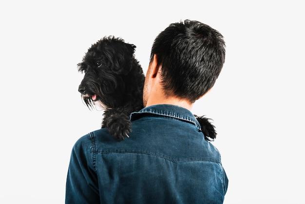 Junger mann, der seinen hund umarmt