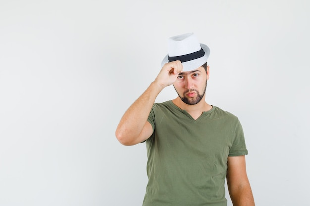 Junger mann, der seinen hut im grünen t-shirt berührt und ernst aussieht